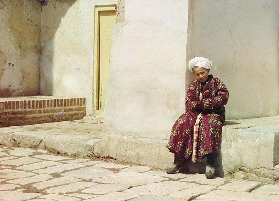 Anak laki-laki sedang duduk di masjid istana Tilla–Kari di Samarkand (sekarang Uzbekistan).