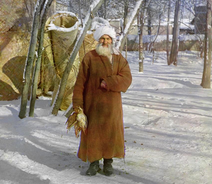 Seorang pria tua yang membawa burung di tengah salju.