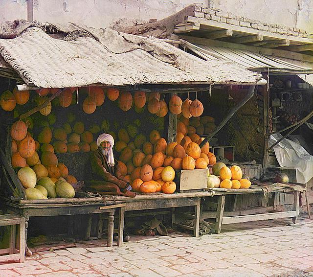 Seorang penjual buah sedang duduk di kios pasar.